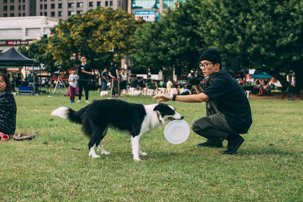 man holding black n white dog